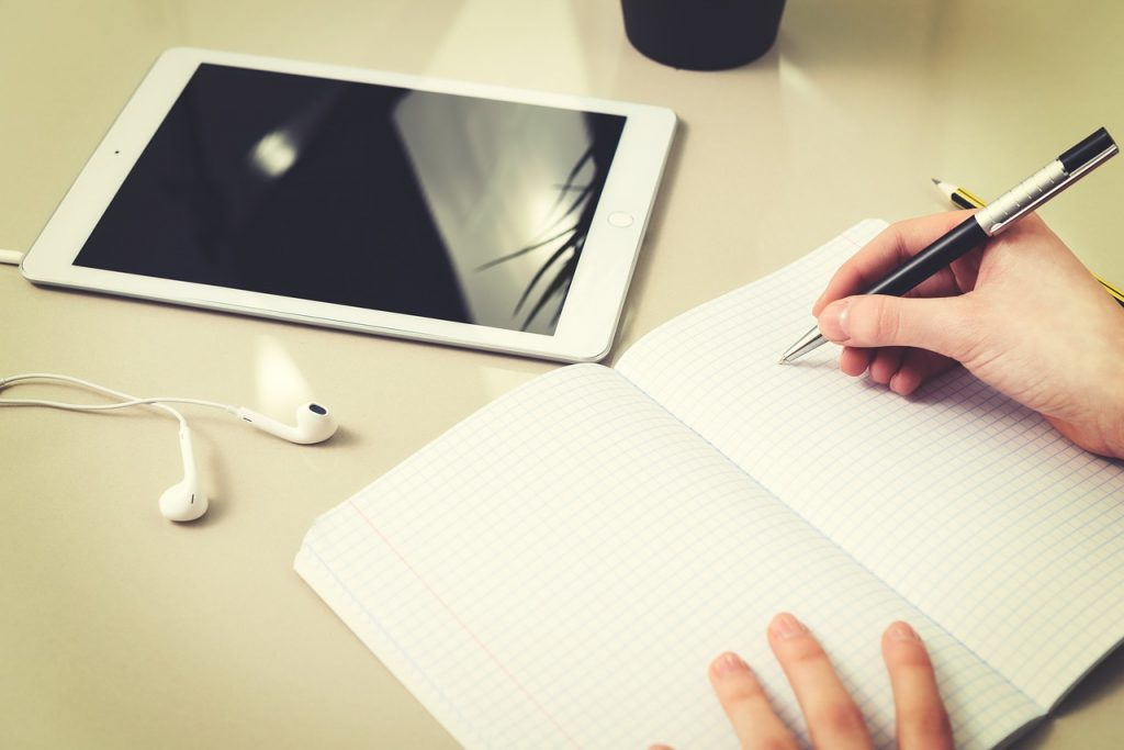 Stock photo of ipad, earbuds, and a blank notebook.